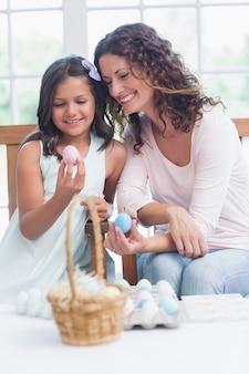 Heureuse mère et fille tenant des oeufs de pâques