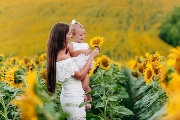 Heureuse mère avec la fille sur le terrain avec des tournesols. maman et bébé femme s'amuser en plein air. concept de famille. fête des mères