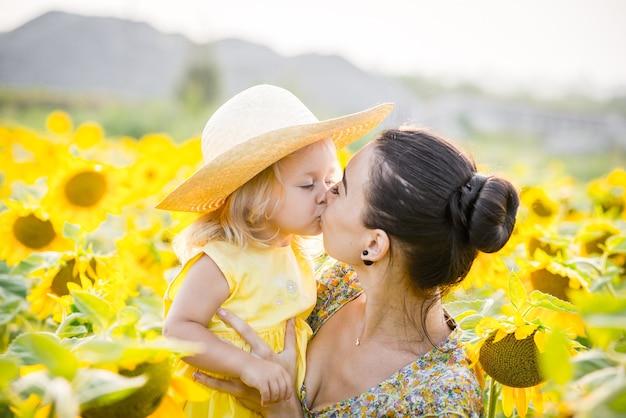 Heureuse mère avec la fille sur le terrain avec des tournesols