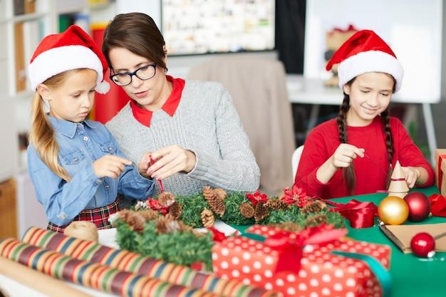 Heureuse mère et filles décorant la guirlande de noël