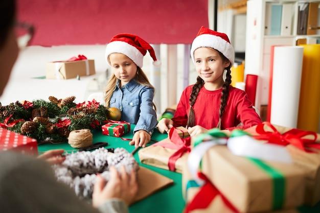 Heureuse mère et filles emballant des cadeaux de noël