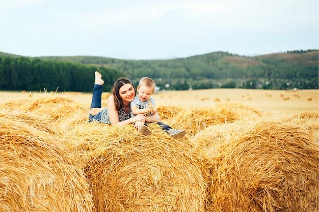 Heureuse mère avec fils en été au champ et paille botte de foin