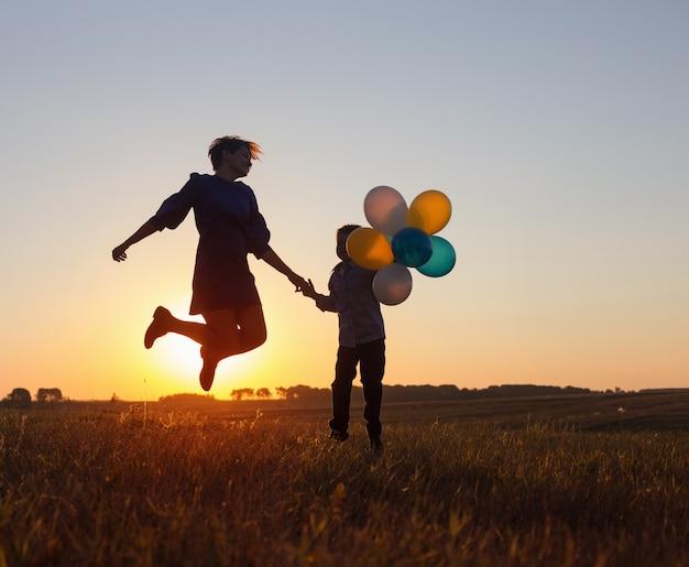 Heureuse mère et fils sautant avec des ballons en plein air