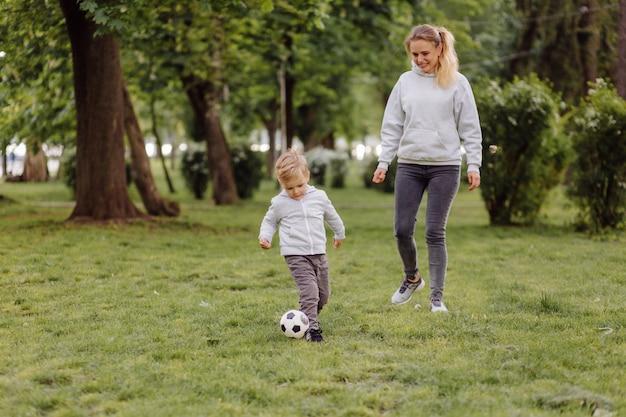 Heureuse mère et fils souriants jouant avec un ballon de football en plein air