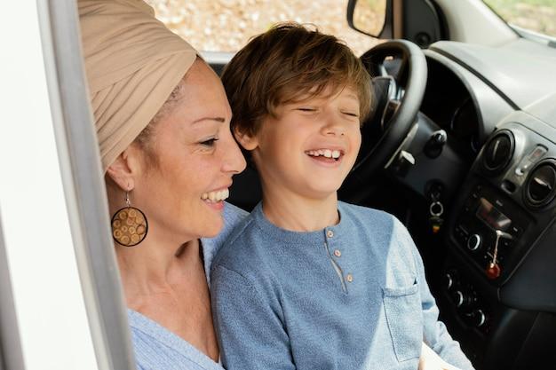 Heureuse mère avec fils en voiture voyageant