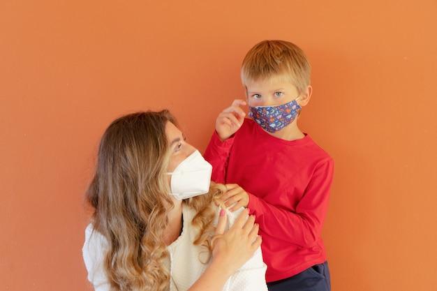 Heureuse mère et garçon souriants portant des masques de protection pendant la période de pandémie de coronavirus, mode de vie de retour à l'école