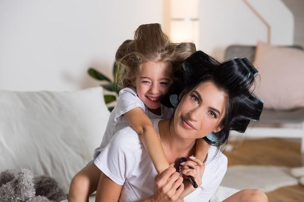 Heureuse mère et jeune fille à la maison. concept de gens de famille heureux mère et enfant étreindre, souriant.