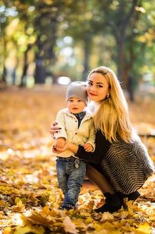 Heureuse mère jouant avec bébé dans le parc à l'automne. kid souriant à maman sur les mains