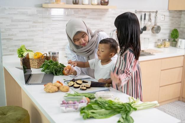 Heureuse mère musulmane et ses enfants cuisinent et s'amusent ensemble à la maison pour préparer le dîner de l'iftar