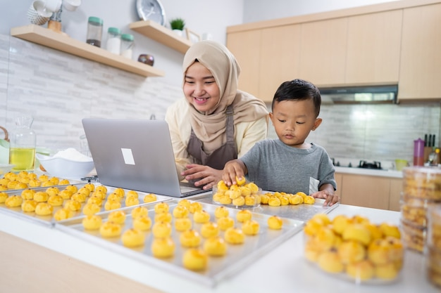 Heureuse mère musulmane travaillant à domicile pour faire la commande de nourriture de gâteau à l'ananas nastar