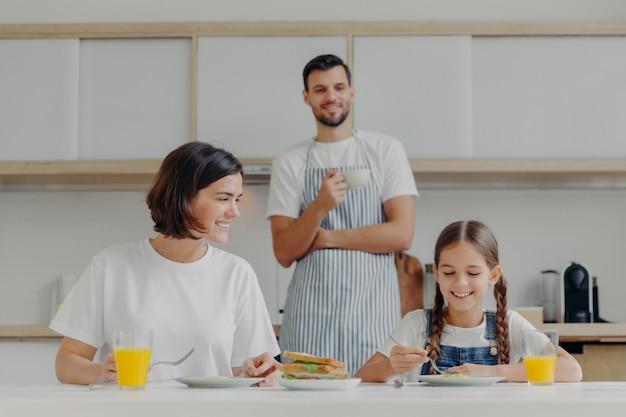 Heureuse mère parle à sa fille pendant le petit déjeuner. père se tient derrière, a préparé un délicieux plat pour la famille.