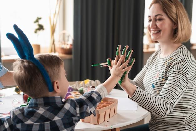 Heureuse mère peignant des mains de fils pour pâques