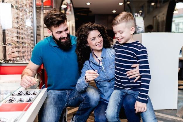 Heureuse mère et père choisissant une monture de lunettes pour leur fils dans un magasin d'optique.