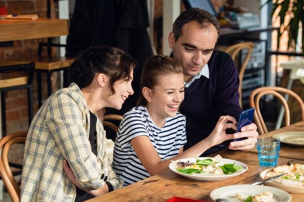 Heureuse mère, père et leur fille en train de dîner et de parler dans un restaurant ou un café