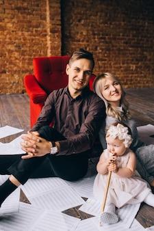 Heureuse mère, père, petite fille se trouvent sur le sol dans la chambre
