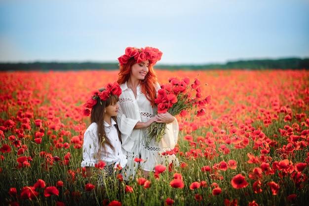 Heureuse mère et petite fille debout dans un champ fleuri dans des couronnes de fleurs de pavot sauvage
