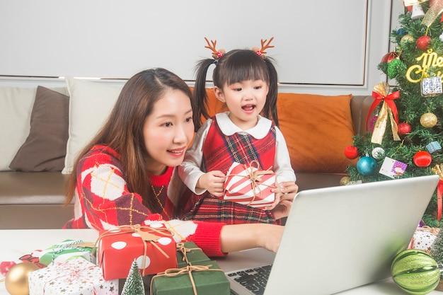 Heureuse mère et petite fille décorant un arbre de noël et des cadeaux à la maison