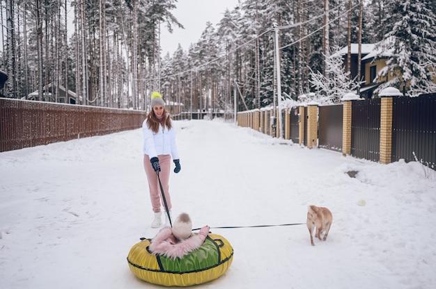 Heureuse mère et petite fille mignonne en vêtements chauds rose à pied s'amusant promenades tube de neige gonflable avec chien rouge shiba inu dans la campagne d'hiver blanc neigeux à l'extérieur