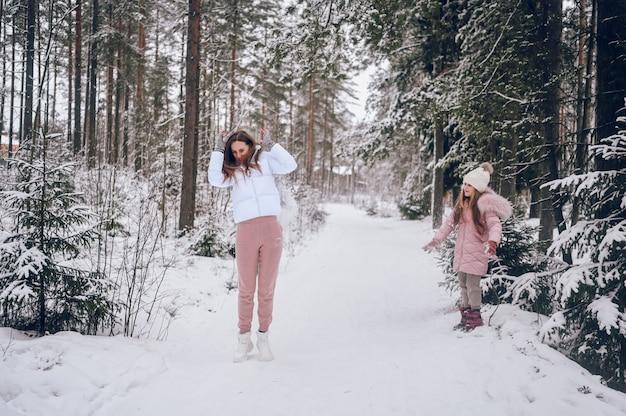 Heureuse mère et petite fille mignonne en vêtements chauds roses marchant jouant bataille de boules de neige s'amusant