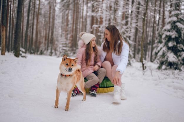 Heureuse mère et petite fille mignonne en vêtements chauds roses marchant s'amusant promenades tube à neige gonflable
