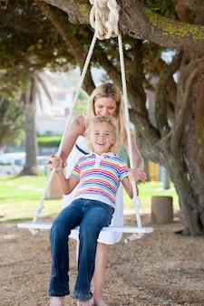 Heureuse mère poussant sa fille sur une balançoire