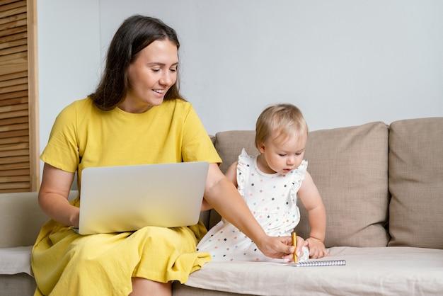 Heureuse mère prenant des notes pour l'enfant tout en travaillant à domicile en multitâche en raison d'un congé de maternité