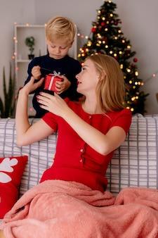 Heureuse mère en robe rouge assise sur un canapé souriant tandis que son petit enfant debout derrière donne un cadeau à sa mère dans une pièce décorée avec un arbre de noël dans le mur
