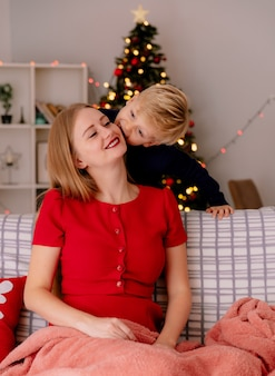 Heureuse mère en robe rouge assise sur un canapé souriant tandis que son petit enfant debout derrière embrassant sa mère dans une pièce décorée avec un arbre de noël dans le mur