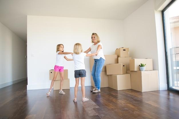 Heureuse mère ronde danser avec deux filles parmi les boîtes non emballées