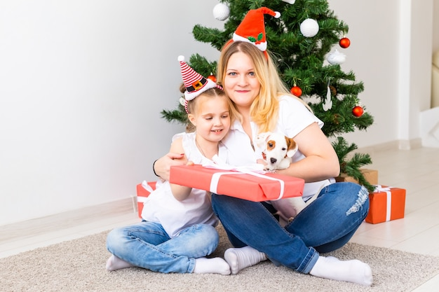 Heureuse mère avec sa fille et chien jack russell terrier assis près de l'arbre de noël