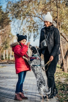 Heureuse mère et sa fille jouant avec un chien dans le parc en automne
