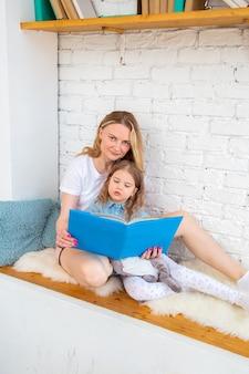 Heureuse mère avec sa fille lisant un livre et souriante assise par terre dans le salon