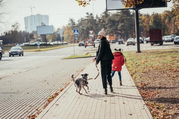 Heureuse mère et sa fille marchent avec chien dans la rue.