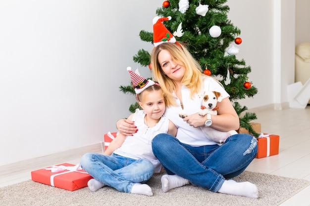 Heureuse mère avec sa fille et son chien jack russell terrier assis près de l'arbre de noël