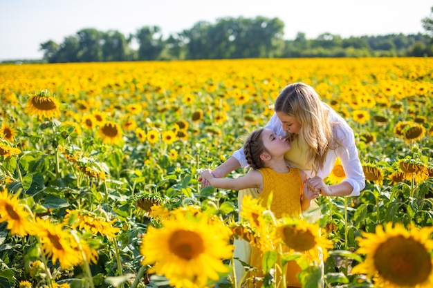 Heureuse mère et sa petite fille dans le champ de tournesol