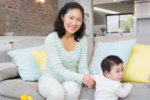 Heureuse mère avec sa petite fille dans le salon à la maison