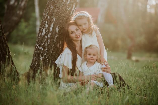 Heureuse mère et ses deux filles dans le parc. scène de nature beauté avec style de vie de famille en plein air. s'amuser en plein air. bonheur et harmonie dans la vie de famille.