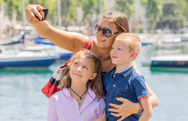 Heureuse mère avec ses enfants prennent un selfie dans une journée ensoleillée