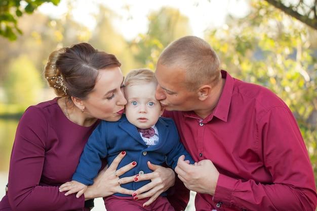 Heureuse mère et son père embrassent son fils dans le parc. le bonheur dans la vie de famille le jour d'été.