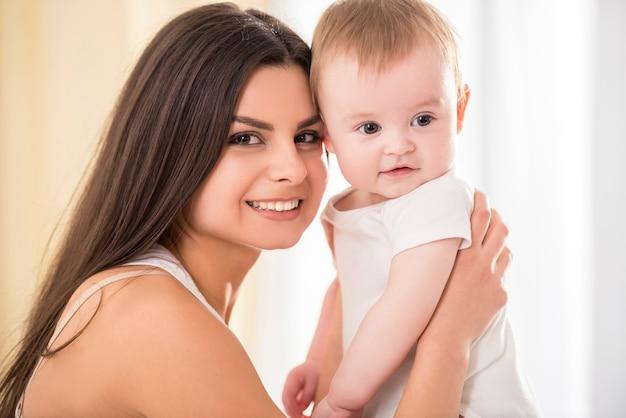 Heureuse mère avec son petit bébé dans sa chambre.