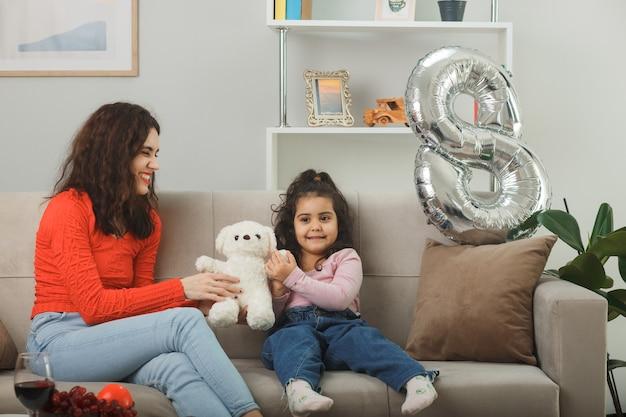 Heureuse mère et son petit enfant assis sur un canapé avec un ours en peluche et un ballon en forme de numéro huit souriant joyeusement dans un salon lumineux