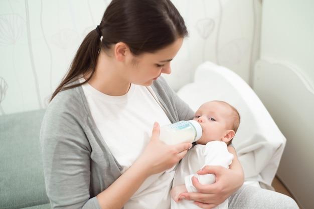Heureuse mère souriante et bébé stting sur le lit à la maison et le bébé mange du lait.