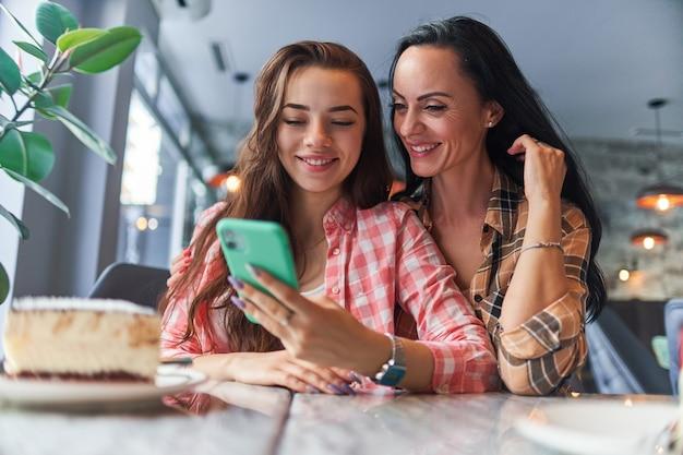 Heureuse mère souriante et joyeuse fille adolescente, regarder du contenu vidéo sur le téléphone et passer du bon temps ensemble dans un café