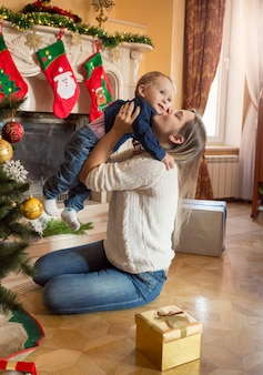 Heureuse mère souriante et son bébé de 1 an posant à l'arbre de noël