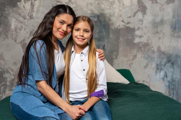 Heureuse mère souriante tendre embrasse sa jolie fille assise sur le lit