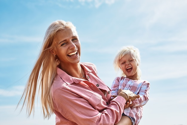 Heureuse mère tenant bébé souriant sur un champ de blé au soleil
