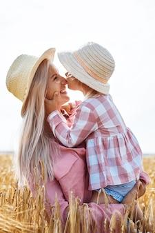 Heureuse mère tenant un bébé souriant sur un champ de blé au soleil.