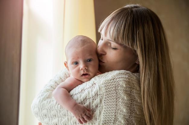 Heureuse mère tenant son bébé à la maison par la fenêtre