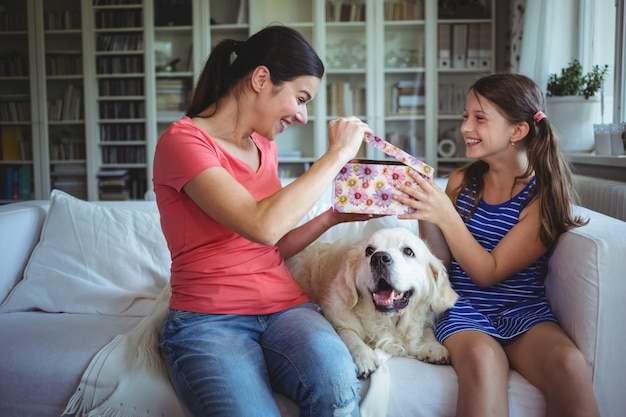 Heureuse mère vérifiant le cadeau surprise donné par la fille