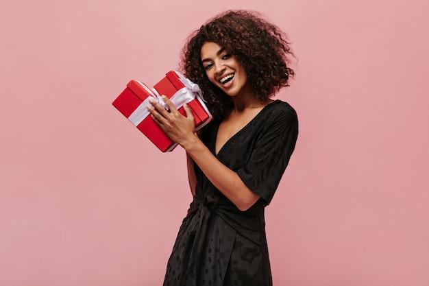 Heureuse merveilleuse femme mulâtre aux cheveux bruns bouclés en robe noire à pois souriant, regardant dans la caméra et tenant deux coffrets cadeaux rouges